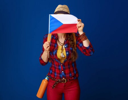 active woman hiker with backpack hiding behind the flag of Czech on blue background