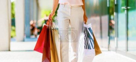 Photo pour Gros plan sur la jeune femme avec des sacs à provisions sur la ruelle du centre commercial - image libre de droit