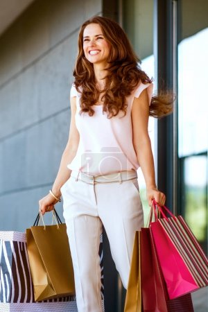 Photo for Young woman with shopping bags walking out from shop - Royalty Free Image