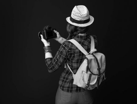 Seen from behind healthy tourist woman with backpack and DSLR camera taking photo