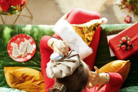 Photo pour Temps des fêtes. Vue supérieure de la jeune femme stressée en or brillant paillettes santa chapeau assis sur divan dans le salon moderne à Noël . - image libre de droit
