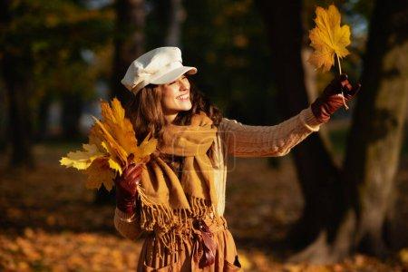 Photo pour Bonjour l'automne. heureuse élégante femme de 40 ans en pull, jupe, chapeau, gants et écharpe à l'extérieur dans le parc d'automne en regardant la feuille jaune . - image libre de droit