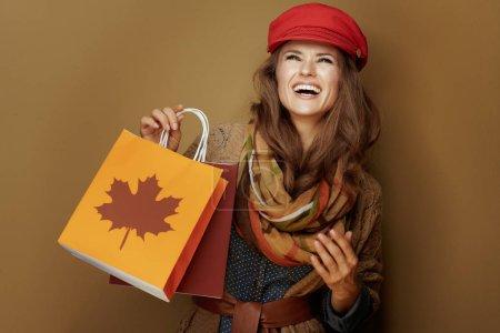 Photo pour Femme d'âge moyen souriante en bonnet rouge, écharpe, chemise en jean et cardigan avec sacs à provisions d'automne regardant vers le haut à l'espace de copie sur fond beige . - image libre de droit