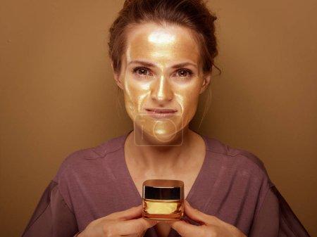 Photo pour Portrait de femme élégante de 40 ans avec masque cosmétique doré tenant bouteille de crème faciale sur fond de bronze . - image libre de droit