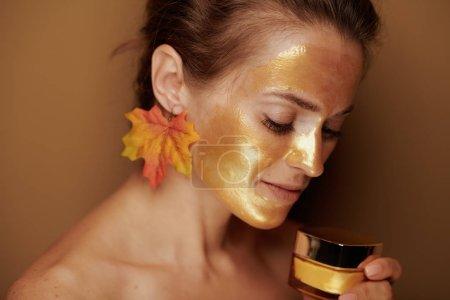 Photo pour Verticale de femme moderne avec le masque de visage cosmétique d'or et la boucle d'oreille de feuille d'automne retenant le pot de produit cosmétique sur le fond en bronze. - image libre de droit