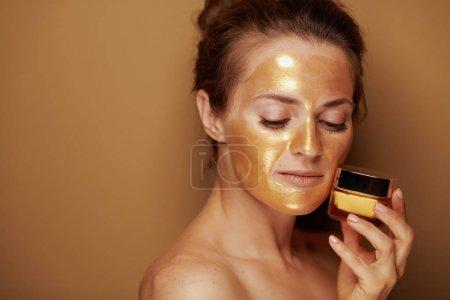 Photo pour Portrait de femme de 40 ans avec masque cosmétique doré tenant un bocal cosmétique isolé sur beige . - image libre de droit