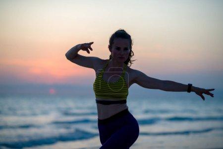 Photo pour Silhouette de femme de sport en forme en tenue de sport sur la plage en soirée faisant de l'entraînement aux arts martiaux. - image libre de droit