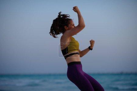 Photo pour Femme de fitness dans des vêtements de style sportif sur la côte de l'océan dans la séance d'entraînement du soir . - image libre de droit