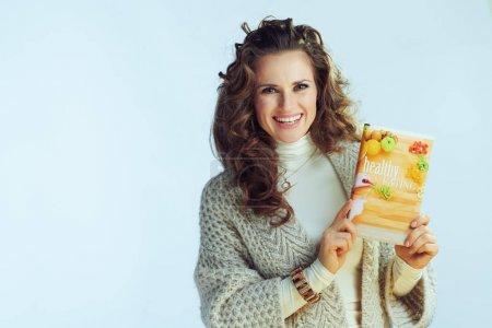 Photo pour Heureuse femme élégante avec de longs cheveux ondulés dans le col pull et cardigan montrant livre de saine alimentation isolé sur hiver bleu clair . - image libre de droit