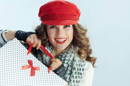 Photo pour Portrait de femme heureuse à la mode avec de longs cheveux bruns en pull, écharpe et chapeau rouge avec des sacs à provisions sur fond bleu clair d'hiver . - image libre de droit