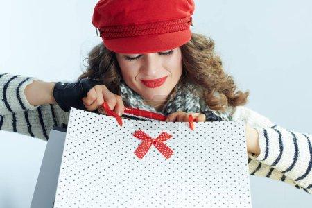 Photo pour Heureuse femme à la mode avec de longs cheveux bruns en pull, écharpe et chapeau rouge avec des sacs à provisions sur fond bleu clair hiver . - image libre de droit
