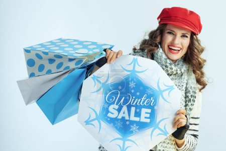 Photo for Portrait of happy elegant woman with long brunette hair in sweater, scarf and red hat with shopping bags showing winter sale banner against winter light blue background. - Royalty Free Image