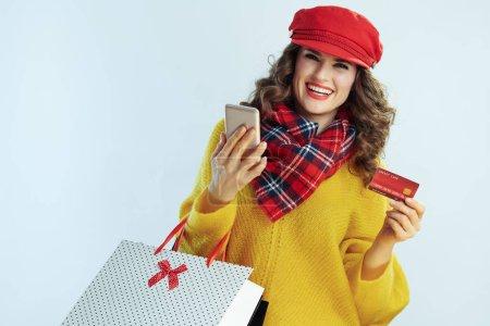 Photo pour Portrait d'une femme heureuse et élégante aux longs cheveux brunette en chandail, écharpe et chapeau rouge avec sacs à provisions et carte de crédit et téléphone intelligent achetant sur Internet isolé sur fond bleu clair d'hiver. - image libre de droit
