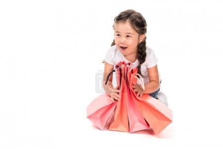Photo pour Excité asiatique enfant avec shopping sacs, isolé sur blanc - image libre de droit
