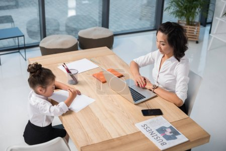 asian businesswoman with daughter in office