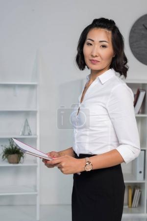 asian businesswoman holding documents