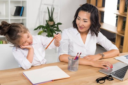 Photo for Asian businesswoman working while her adorable daughter drawing near in modern office - Royalty Free Image