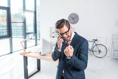 Photo for Young businessman talking on smartphone and triumphing at workplace - Royalty Free Image