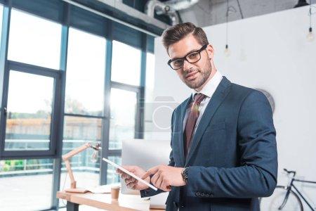 Foto de Hombre de negocios usando tableta digital y mirando a la cámara en la oficina - Imagen libre de derechos