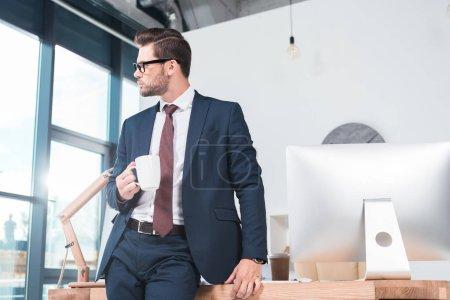 Photo pour Beau jeune homme d'affaires dans des lunettes tenant tasse de café et regardant loin dans le bureau - image libre de droit