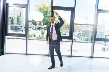 Photo pour Souriant le jeune homme d'affaires avec ordinateur portable et le smartphone à la recherche de suite au bureau - image libre de droit