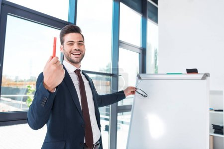 Photo for Handsome young businessman holding pen and smiling at camera while standing near whiteboard in office - Royalty Free Image