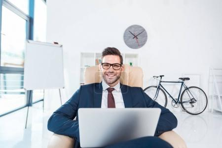 Photo for Handsome young businessman in eyeglasses using laptop and smiling at camera in office - Royalty Free Image
