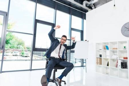 Photo for Excited young businessman triumphing and raising hands while sitting on chair in office - Royalty Free Image