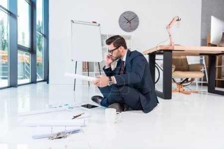 Photo for Side view of businessman working with papers and devices while sitting on floor in office - Royalty Free Image