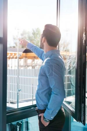 businessman pointing at window