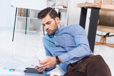 hombre de negocios con smartphone y documentos