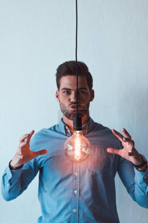 Photo for Young businessman with light bulb between hands looking at camera on grey - Royalty Free Image
