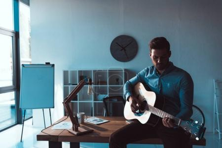 businessman with guitar in office