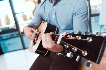 Photo pour Recadrée tir du jeune homme d'affaires jouant de la guitare au bureau - image libre de droit