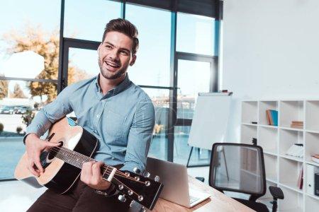 Photo pour Beau jeune homme d'affaires souriant jouant de la guitare au bureau - image libre de droit