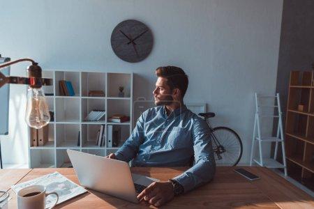 Photo pour Beau jeune homme d'affaires utilisant un ordinateur portable et regardant loin dans le bureau - image libre de droit
