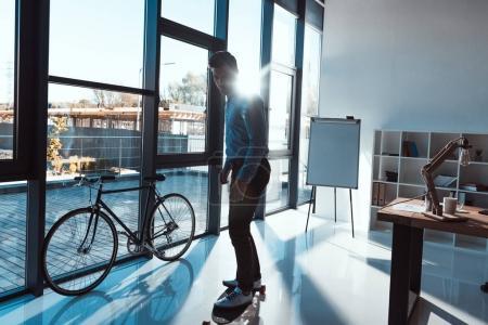 Photo pour Vue complète de jeune homme d'affaires debout sur le skateboard dans le bureau - image libre de droit