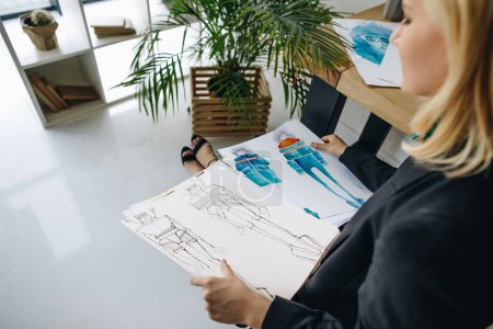 Photo for Cropped shot of young blonde fashion designer holing sketches at workplace - Royalty Free Image
