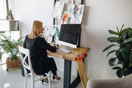 Foto de Atractivo joven diseñador de moda usando tableta gráfica y computadora de escritorio en lugar de trabajo - Imagen libre de derechos