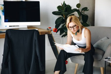 Photo for Young female fashion designer in eyeglasses looking at sketchea in office - Royalty Free Image