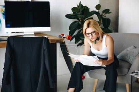 Foto de Joven diseñadora de moda mujer en gafas mirando sketchea en oficina - Imagen libre de derechos