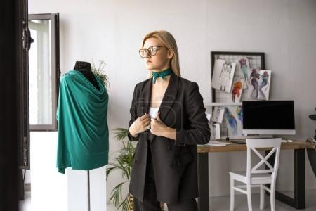 Photo pour Belle jeune styliste en lunettes de vue à la recherche de suite en se tenant debout près de mannequin au bureau - image libre de droit