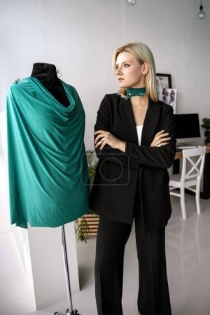 Photo pour Confiant jeune modiste debout près de mannequin et la recherche. - image libre de droit