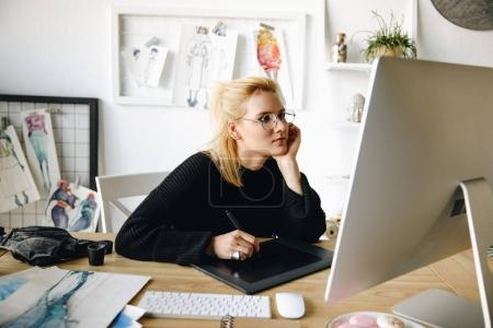 Photo for Focused young fashion designer in eyeglasses using graphic tablet and desktop computer - Royalty Free Image