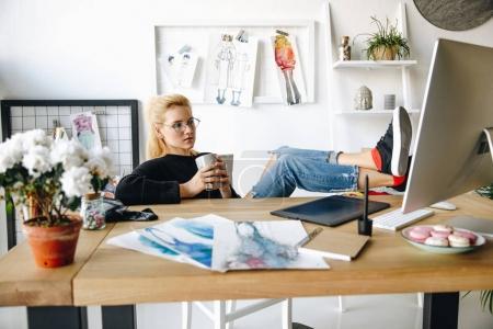 Foto de Atractivo joven diseñador de moda en gafas bebiendo café y usando la computadora de escritorio en la oficina - Imagen libre de derechos
