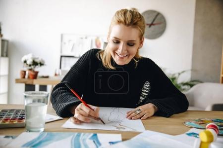 Photo pour Joyeux jeune créateur de mode dessin aquarelle croquis sur le lieu de travail - image libre de droit