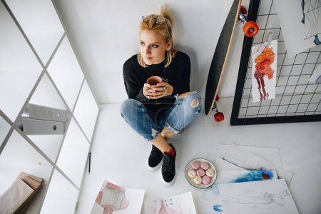 Foto de Vista de ángulo alto de pensativo joven diseñador de moda beber café y comer macarrones en oficina - Imagen libre de derechos