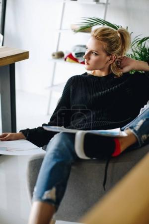 Foto de Hermosa chica rubia pensativa mirando, sentado en la oficina - Imagen libre de derechos