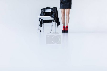 Photo for Fashionable girl standing at chair with black leather jacket, isolated on white - Royalty Free Image