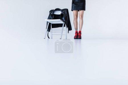 Photo pour Fille à la mode, debout sur une chaise avec la veste en cuir noir, isolée sur blanc - image libre de droit